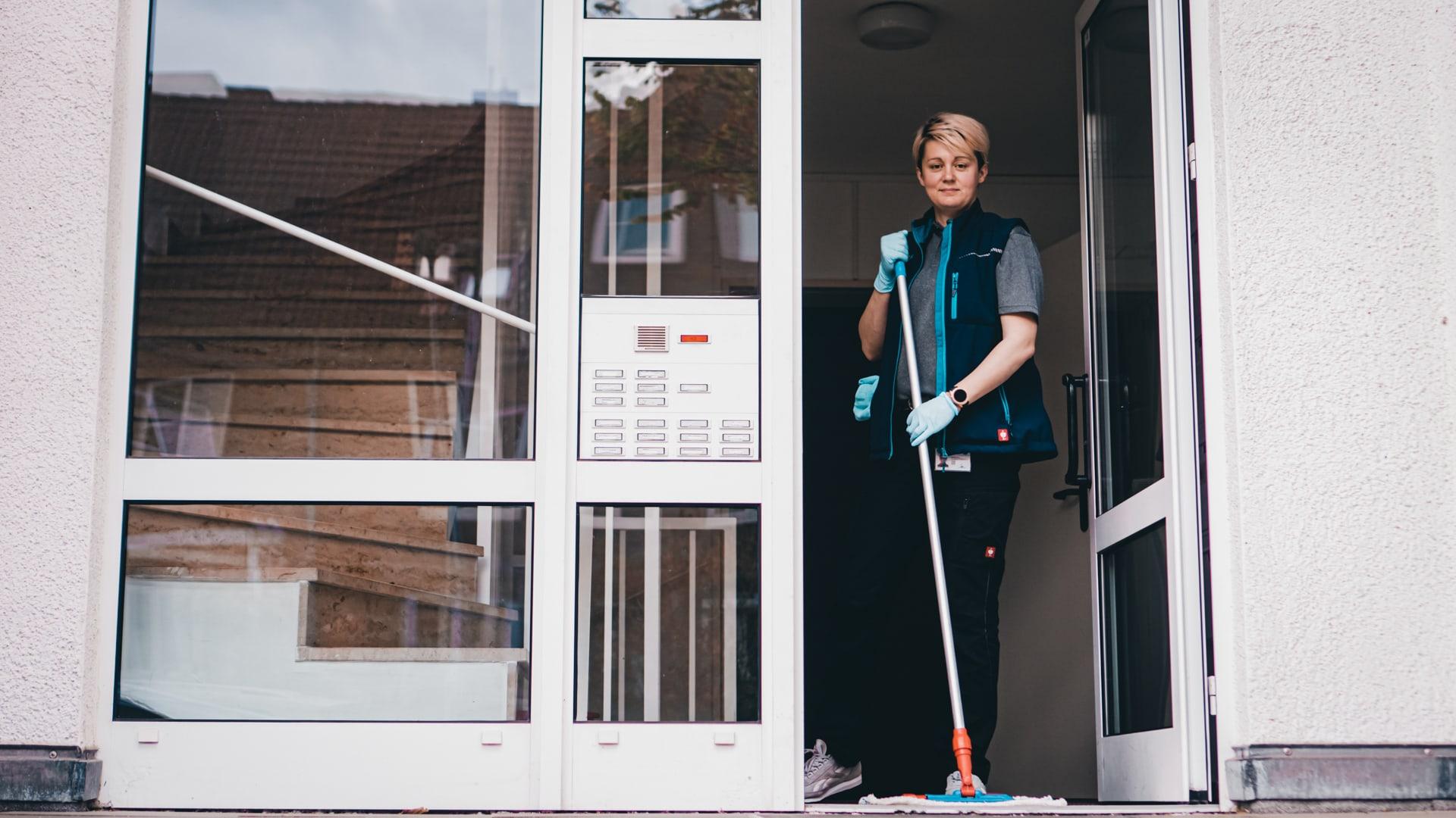 Optima Reinigungskraft während einer Treppenhausreinigung